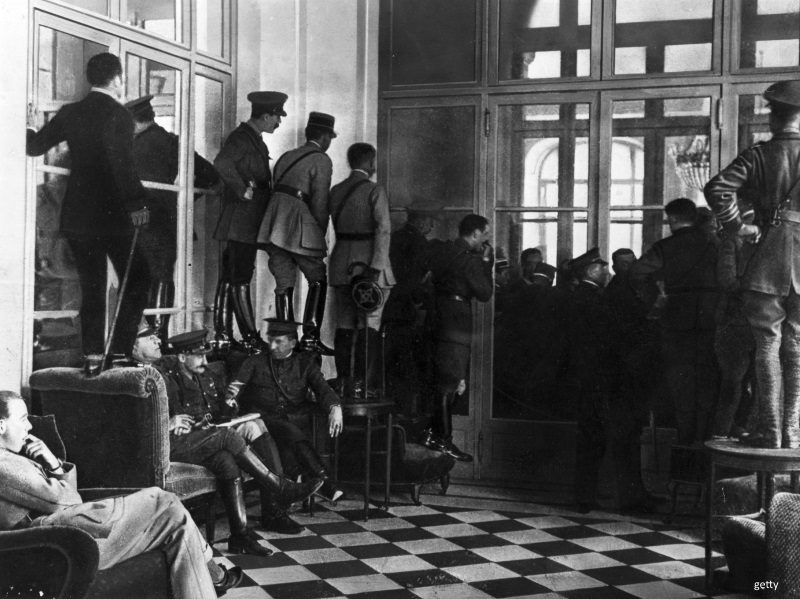 Soldiers watch the signing of the Treaty of Versailles.